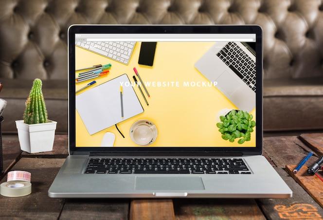 Laptopa makieta na drewnianym stole
