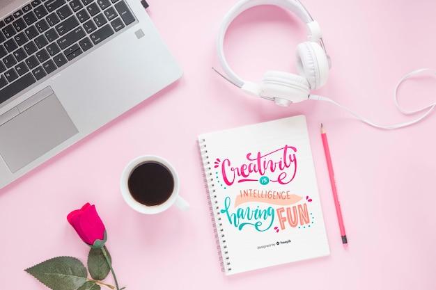 Laptopu hełmofon i notatnik na różowym tle