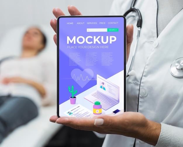 Lekarz trzymając tabletkę makiety w pobliżu pacjenta