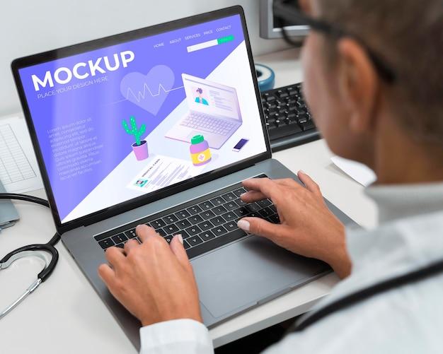 Lekarz za pomocą makiety laptopa