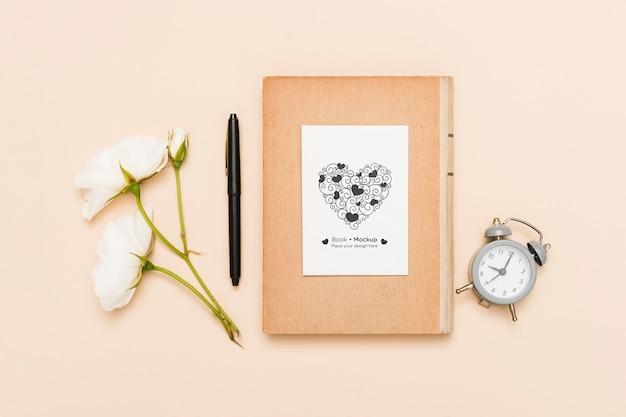 Leżał płasko z książką z zegarem i różami
