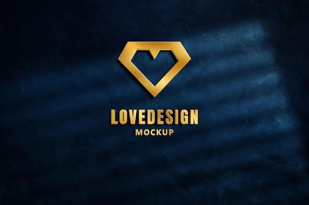 Logo makieta 3d złoty metal z wytłoczonym stylem na ciemnoniebieskiej betonowej ścianie.