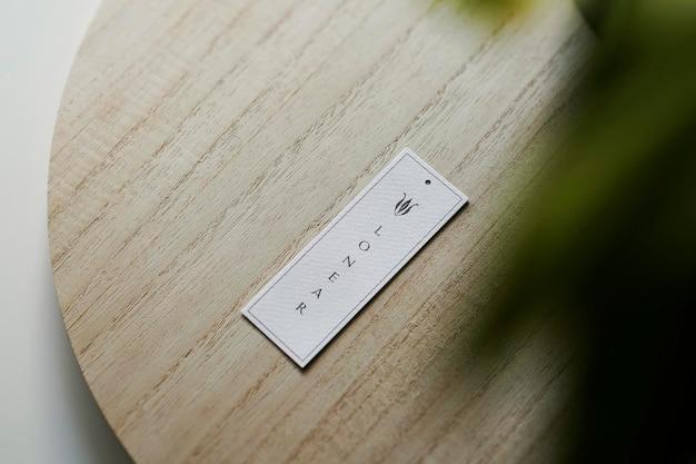Logo makieta tag na drewnie z rośliną