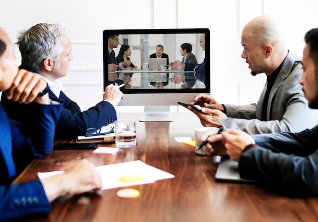 Ludzie biznesu mający spotkanie konferencyjne przy użyciu makiety ekranu komputera