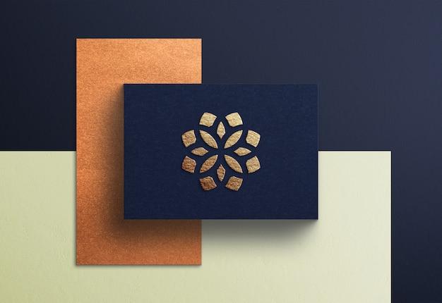 Luksusowa makieta złotego logo na wytłoczonej niebieskiej wizytówce