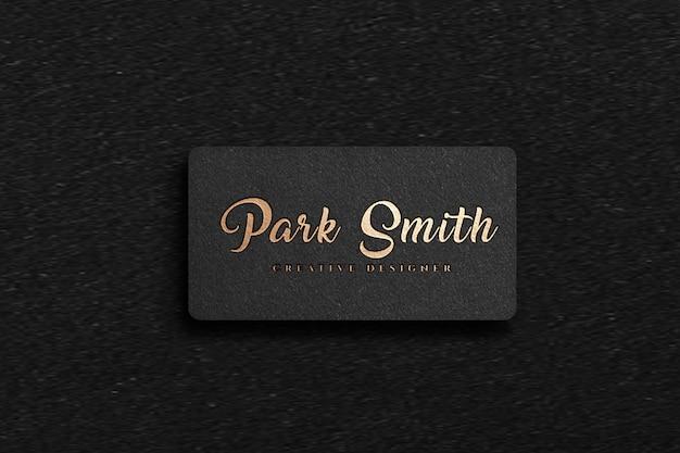 Luksusowe złote logo i makieta wizytówki na czarnym papierze rzemieślniczym
