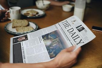 Mężczyzna czyta wiadomość przy śniadaniowym stołem