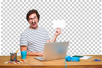Młody szalony projektant graficzny na biurku z laptopem iz plakatem