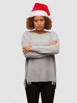 M? oda czarna kobieta ma na sobie kapelusz santa skrzy? owania broni zrelaksowany