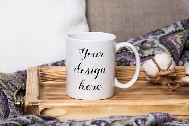 Makieta białego kubka do kawy na drewnianej tacy w przytulnym wnętrzu