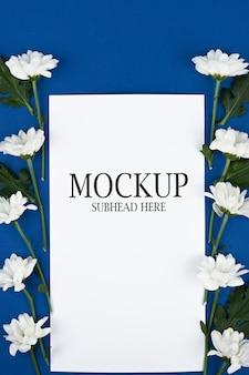 Makieta białego papieru i białych kwiatów na niebieskim tle