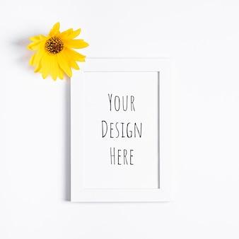 Makieta białej pustej ramki na zdjęcia z żółtym kwiatem
