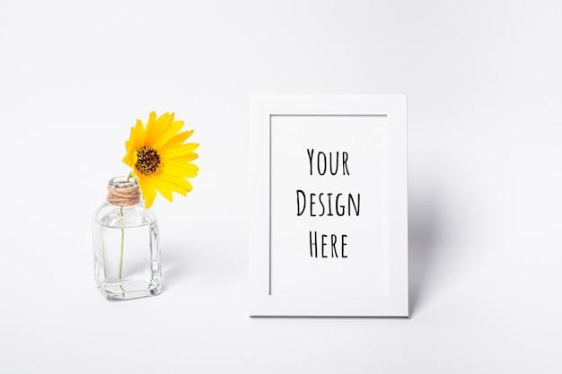 Makieta białej pustej ramki na zdjęcia z żółtym kwiatkiem w szklanym słoju