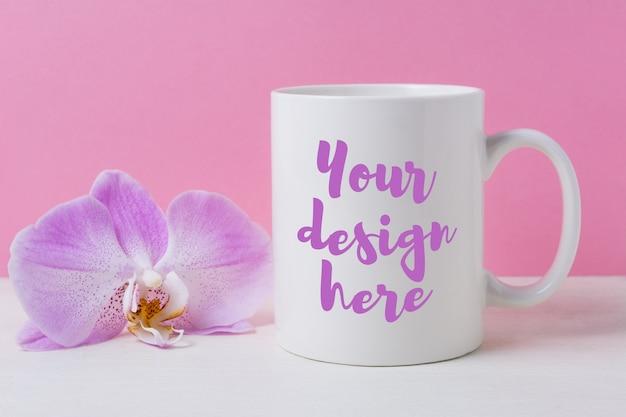 Makieta biały kubek kawy z fioletową orchideą