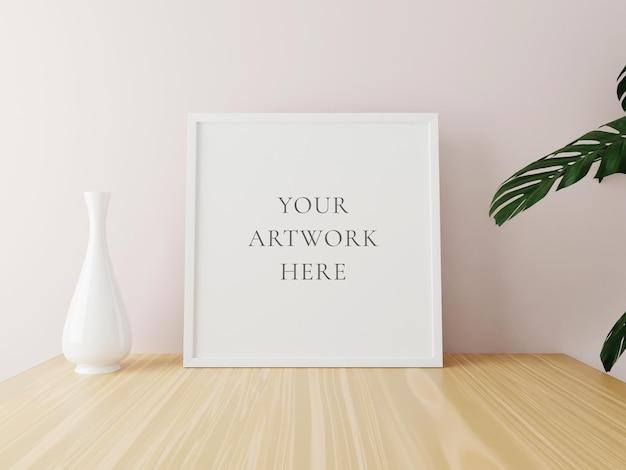 Makieta biały kwadrat ramki na drewnianym stole z wazonem i roślinami. renderowania 3d.