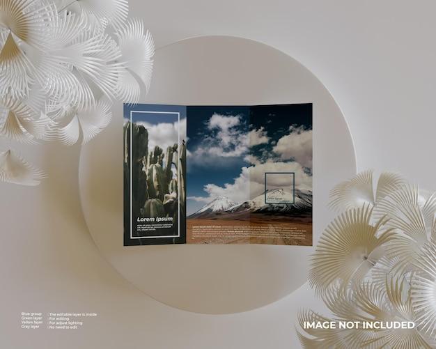 Makieta broszury trifold z podium i białą rośliną z boku wygląda na widok z góry