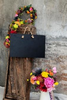 Makieta czarnej pustej tablicy kwiatowej w ogrodzie