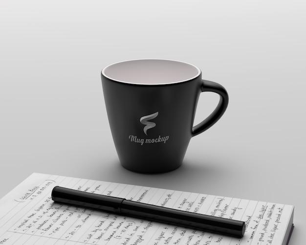 Makieta czarny kubek kawy z notebookiem