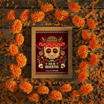 Makieta czerwonej czaszki otoczona pomarańczowymi kwiatami