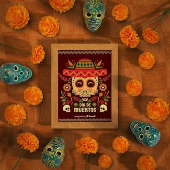 Makieta dia de muertos otoczona czaszkami i kwiatami
