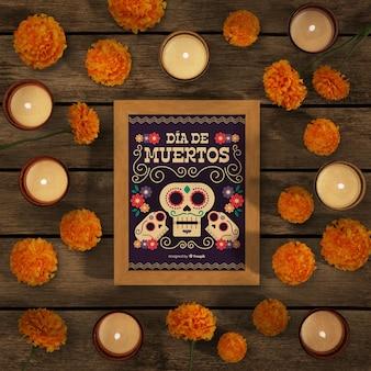 Makieta dia de muertos otoczona kwiatami i świecami