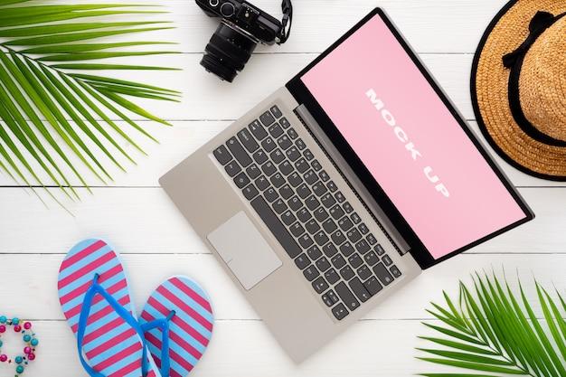 Makieta do wyświetlania laptopa na białym drewnianym stole na letnie wakacje