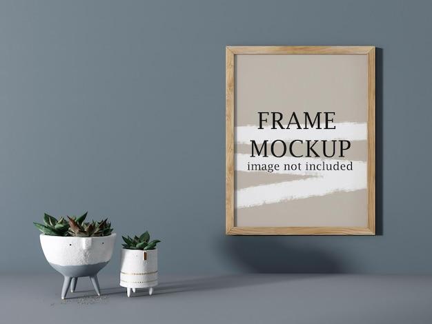 Makieta drewniana ramka na zdjęcia na szarej ścianie obok rośliny