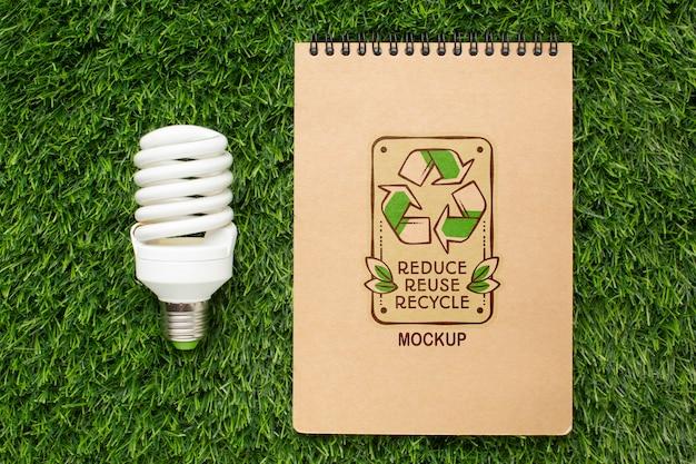Makieta ekologicznego notatnika z widokiem z góry z żarówką