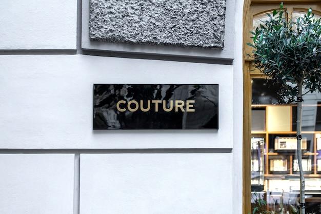 Makieta eleganckiej czarnej kamiennej płyty ze złotym logo na fasadzie sklepu