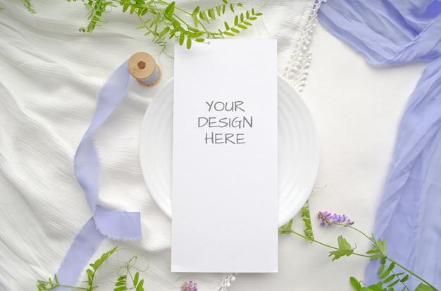 Makieta karta menu z fioletowymi kwiatami i delikatnymi jedwabnymi wstążkami na białym tle.