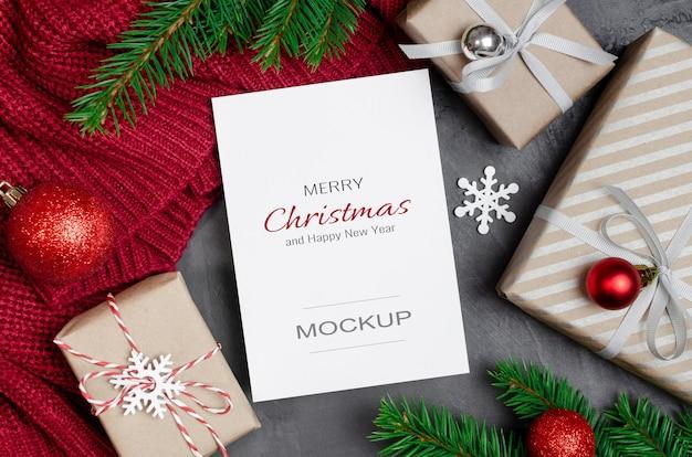 Makieta kartki świątecznej lub noworocznej z ozdobnymi pudełkami prezentowymi i gałęziami jodły