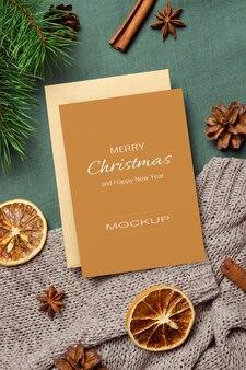 Makieta kartki świątecznej lub noworocznej z suchymi pomarańczami, przyprawami i sosnowymi gałęziami z szyszkami