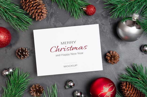 Makieta kartki świątecznej lub noworocznej ze świątecznymi dekoracjami i gałęziami sosny z szyszkami