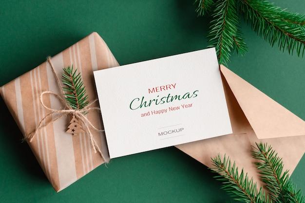 Makieta kartki świątecznej z kopertą, pudełkiem prezentowym i zielonymi gałęziami jodły