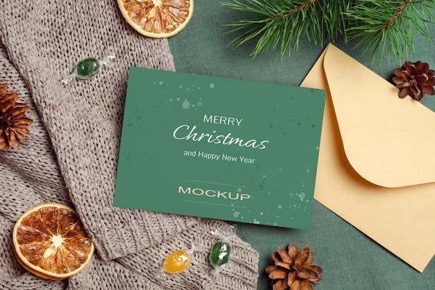 Makieta kartki świątecznej z kopertą, suchymi pomarańczami i gałęziami sosny z szyszkami