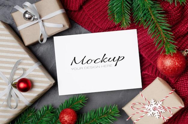 Makieta kartki świątecznej z ozdobnymi pudełkami prezentowymi i gałęziami jodły na dzianym tle