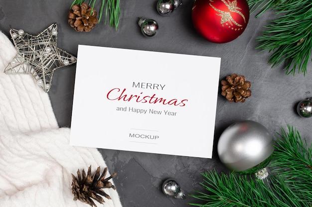 Makieta kartki świątecznej z świątecznymi dekoracjami i gałęziami sosny z szyszkami