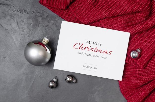 Makieta kartki świątecznej ze srebrnymi świątecznymi dekoracjami na czerwonym tle z dzianiny