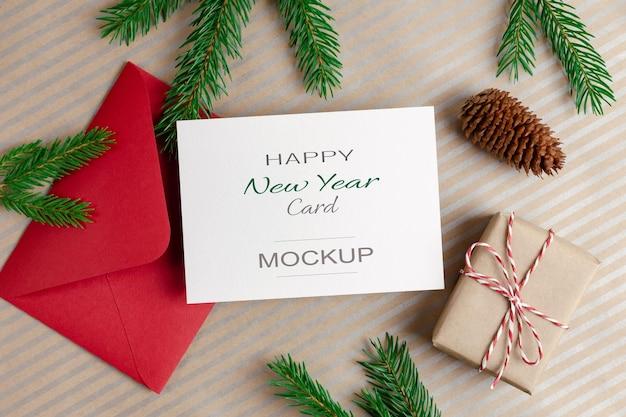 Makieta kartki z życzeniami wesołych świąt z czerwoną kopertą, pudełkiem prezentowym i szyszką jodły