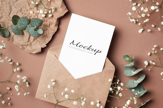 Makieta kartki z życzeniami z kopertą i białymi kwiatami hypsofili i eukaliptusa