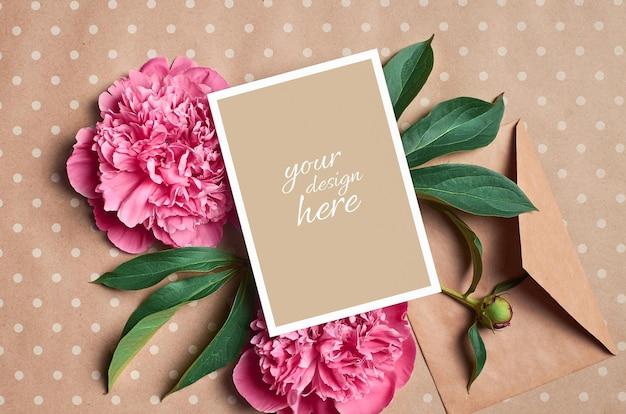 Makieta kartki z życzeniami z kopertą i różowymi kwiatami piwonii na tle papieru rzemieślniczego