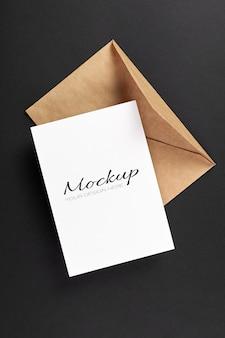 Makieta kartki z życzeniami z kopertą na czarnym tle papieru