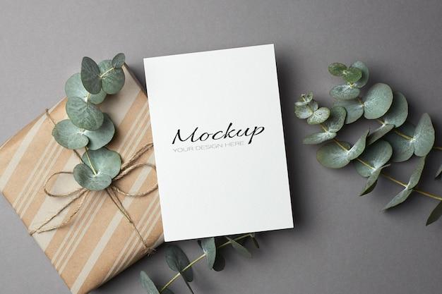 Makieta kartki z życzeniami z pudełkiem prezentowym i świeżymi gałązkami eukaliptusa