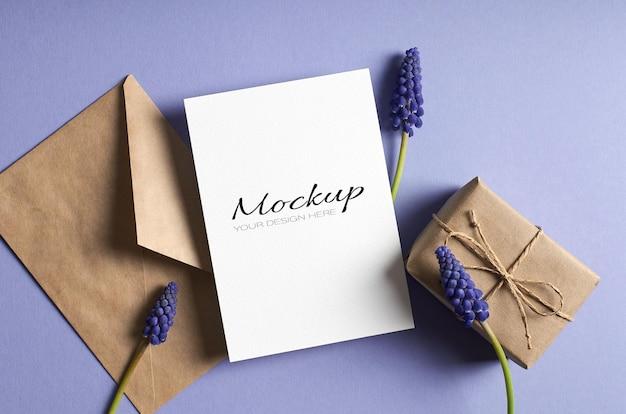 Makieta kartki z życzeniami z pudełkiem prezentowym, kopertą i niebieskimi kwiatami muscari