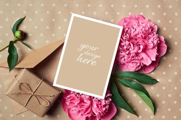 Makieta kartki z życzeniami z pudełkiem prezentowym, kopertą i różowymi kwiatami piwonii