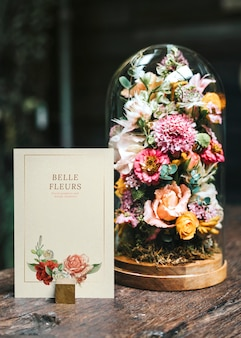 Makieta karty przez bukiet kwiatów na drewnianym stole