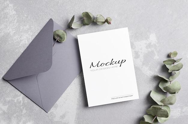 Makieta karty z pozdrowieniami lub zaproszeniem na ślub z kopertą i suchą gałązką eukaliptusa