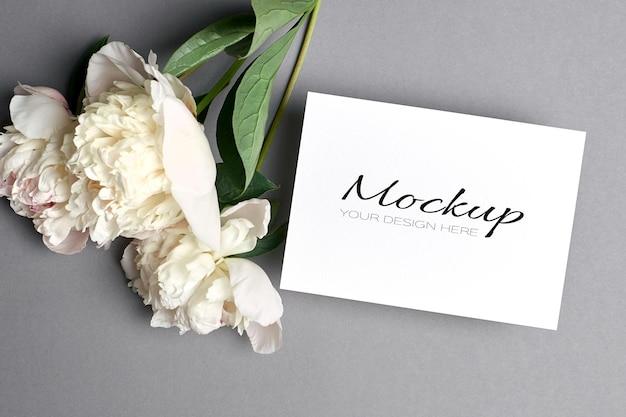 Makieta karty z pozdrowieniami lub zaproszeniem z białymi kwiatami piwonii na szaro