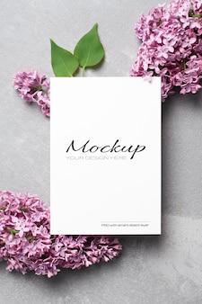 Makieta karty z pozdrowieniami lub zaproszeniem z fioletowymi kwiatami bzu na szaro