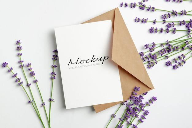 Makieta karty z pozdrowieniami lub zaproszeniem z kopertą i świeżymi kwiatami lawendy na białym tle